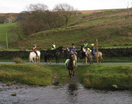 horse riders fording a river